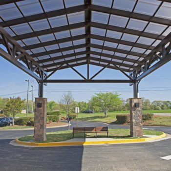 "Standing Seam Skin System Canopy, 25'5"" x 42'6"", 2.5/12 pitch. Glazing: 20mm Bronze Cellular Polycarbonate mounted to steel purlins, structure by others. Includes gutters and downspouts. Finish: Dark Bronze Anodized."